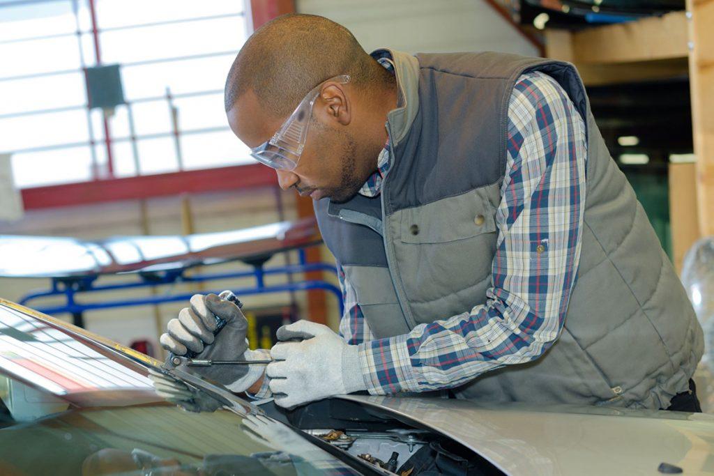 mechanic-using-repairing-equipment-to-fix-damaged-PWJU3PD-1